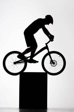 silhouette of trial cyclist balancing on stand on white