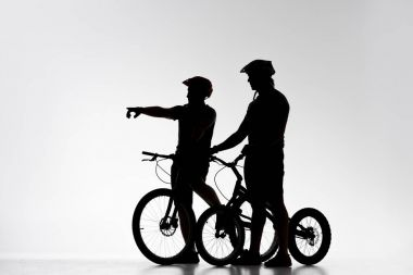 silhouettes of trial cyclists with bicycles chatting on white