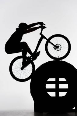 silhouette of trial biker balancing on tractor wheel on white