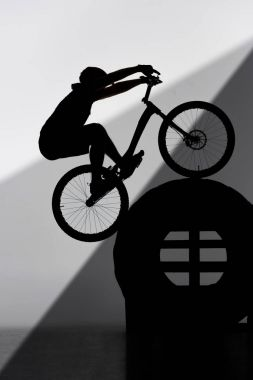 silhouette of trial biker balancing on tractor wheel on grey