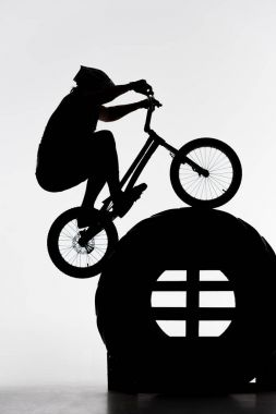 silhouette of trial biker jumping on tractor wheel on white