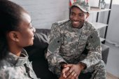 Woman and man in army uniform talking while sitting on sofa