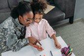 Fényképek Afrikai-amerikai nő az álcázó ruhák és a gyermek rajz együtt