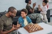 Fényképek Ember a terepszínű ruhák sakkozni, míg anya és lánya együtt játszottak a fia oktatásának