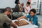 Fényképek A hadsereg egységes sakkozni fia, míg anya és lánya együtt az Atya