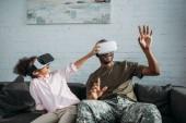 schöner Soldat in Tarnkleidung mit Kind, das mit Virtual-Reality-Headsets spielt