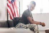 Fotografia Soldato dellesercito femminile in vestiti di camuffamento che si siede sul divano