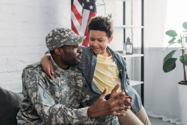 African american boy hugging and listening to his father in army uniform