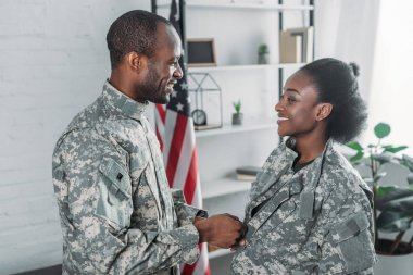 Handsome man helping woman to get dressed in camouflage clothes