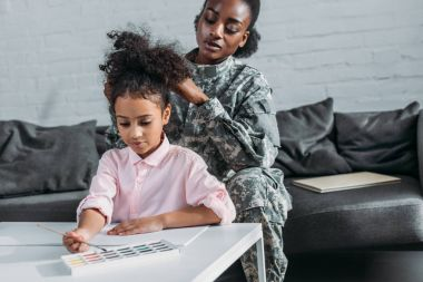 Mother soldier fixing hairstyle of daughter busy with drawing by table
