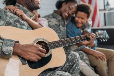 Woman and children listening to father in camouflage clothes playing guitar