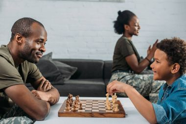 Man in camouflage clothes playing chess with his son while mother and daughter playing together