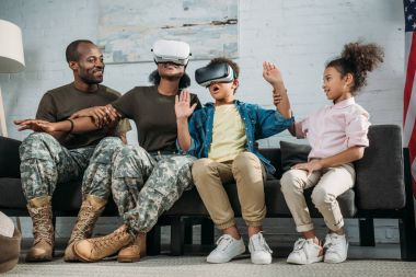 Happy family with children and parents in camouflage clothes using vr glasses