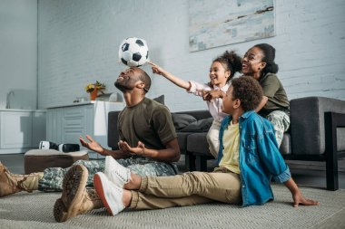 Woman and man in army uniform with their children playing with football ball
