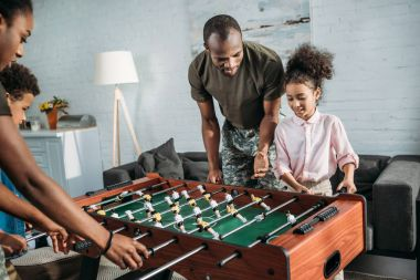 Parents in camouflage clothes playing table football with their kids