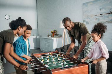 Happy family of soldier parents and african american kids playing table football