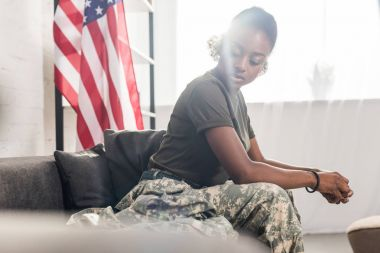 Female army soldier in camouflage clothes sitting on sofa