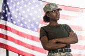Fotografia Soldato dellesercito americano africano femminile in vestiti del camuffamento davanti a noi bandiera