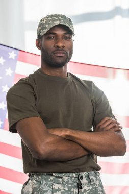 African american soldier with folded arms in front of us flag