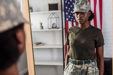 Female army soldier in camouflage clothes posing by the mirror