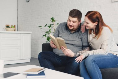 boyfriend and smiling girlfriend reading book together on sofa in living room