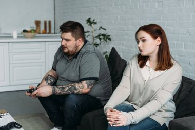 worried girlfriend sitting on sofa while boyfriend playing video game at home