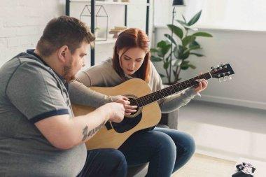 boyfriend teaching girlfriend playing acoustic guitar at home