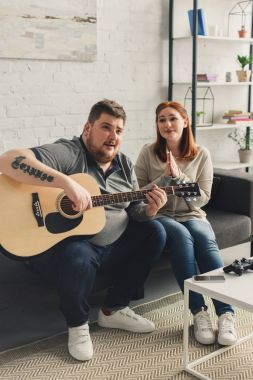 girlfriend asking boyfriend playing song with acoustic guitar at home