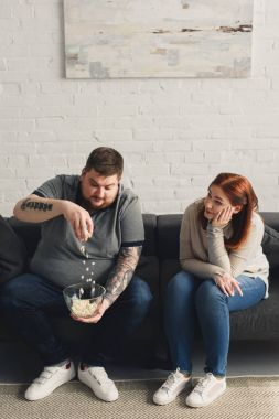 Girlfriend looking how overweight boyfriend playing with popcorn at home