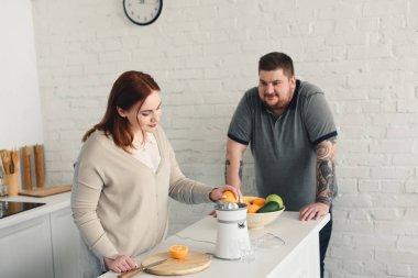 overweight boyfriend and girlfriend preparing orange juice at kitchen