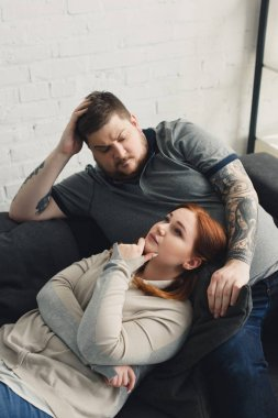 pensive boyfriend and girlfriend lying on sofa at home