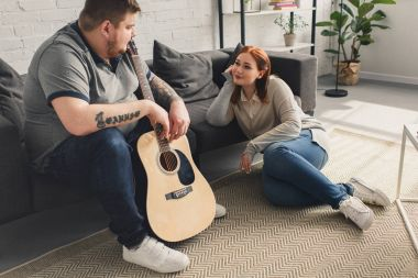 size plus boyfriend holding acoustic guitar and looking at girlfriend at home