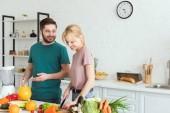 usmívající se pár veganů přípravy jídla v kuchyni