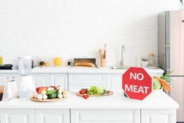 ripe delicious vegetables and no meat sign on kitchen counter