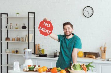 handsome vegan man showing no meat sign in kitchen
