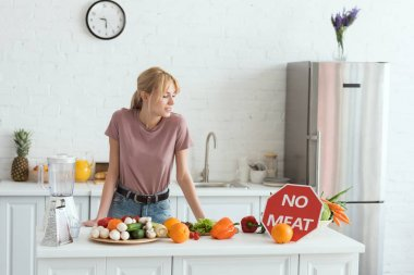 attractive vegan girl looking at no meat sign in kitchen