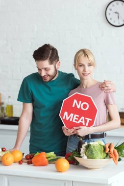 couple of vegans with no meat sign at kitchen