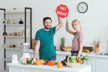 couple of vegans showing no meat sign at kitchen