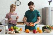 Fotografie paar Vegetarier mit Tablette und Kochrezept in der Küche