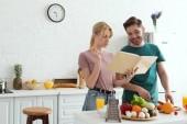 Fotografie pár veganů připravuje salát kuchařka v kuchyni