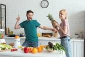 Fotografie usmívající se pár veganů baví při vaření v kuchyni
