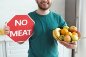Photo partial view of smiling man holding no meat sign and bowl with fresh fruits, vegan lifestyle concept