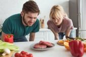 znechucený veganské pár na desku v kuchyni doma při pohledu na syrové maso