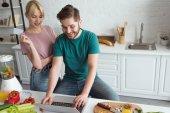 Fotografie Veganská pár s notebookem nákupu zboží přes Internet dohromady v kuchyni doma