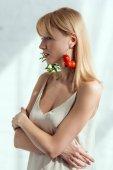 Fotografie atraktivní žena v šatech s náušnice vyrobené z čerstvé rukoly a cherry rajčat, vegan životní styl koncept