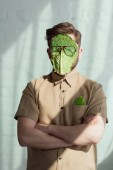 Photo obscured view of man with savoy cabbage leaf and eyeglasses on face, vegan lifestyle concept