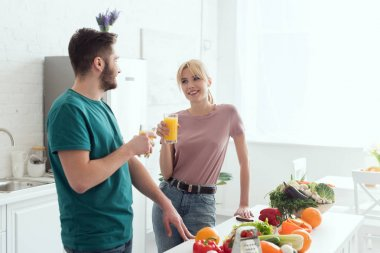 couple of vegans talking at kitchen and holding juice