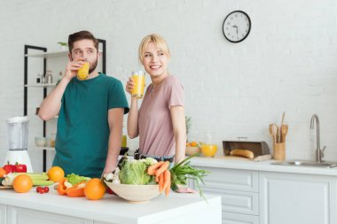 smiling couple of vegans drinking fresh juice at kitchen and looking away