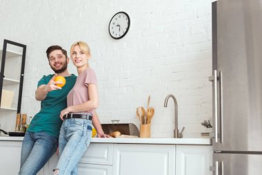 couple of vegans hugging and looking away at kitchen