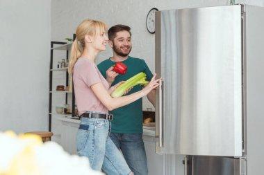couple of vegans taking vegetables from fridge in kitchen